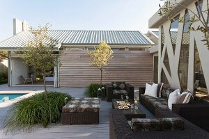 Modern, dark wicker outdoor furniture on spacious terrace