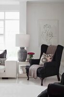 Black wing-back chair in elegant white interior