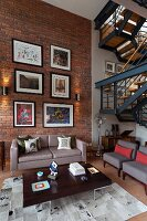 Gallery of pictures on brick wall of loft apartment living room with retro furniture and industrial-style staircase
