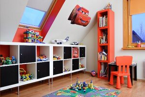 Modern sideboard with alternating open-fronted compartments and black modules, red chair and tall set of shelves in child's attic bedroom