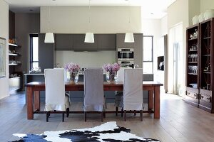Chairs with loose covers in different shades of grey around long dining table, open-plan fitted kitchen in background, colonial-style wooden furniture and animal-skin rug