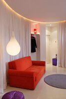 Teardrop-shaped pendant lamp and orange sofa in front of white curtain used as partition in minimalist, circular lounge area