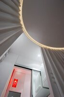View from below of circular ceiling panel with indirect lighting and curtains; orange lamp in bathroom seen through open sliding door