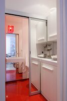 Kitchenette with open mirrored sliding door leading to bathroom with continuous orange floor
