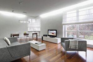 Pale grey, elegant sofa set around low white table opposite TV on low sideboard on elegant walnut parquet floor in modern interior with half-closed roller blinds on French windows