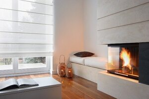 Fireplace next to bench with white seat cushions and candle lanterns on parquet floor in corner in front of French windows with closed roller blinds