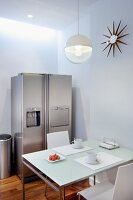 Dining table with breakfast place settings below spherical lamp and stainless steel fridge-freezer in corner