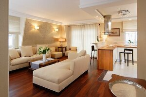 Classic, cream sofa set on exotic wood parquet floor and open-plan kitchen area in background in traditional interior