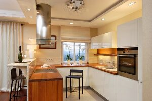 Designer kitchen with white cabinets, wooden worksurface, stainless steel extractor hood and recessed spotlights integrated in ceiling frieze