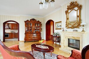 Lounge area with antique coffee table in front of fireplace and mirror with carved, gilt frame on wall in grand living room
