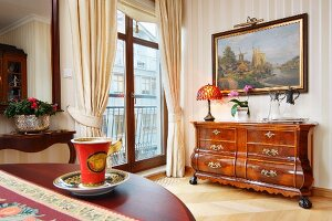 Antique, Art Nouveau coffee cup and saucers on table opposite Baroque-style chest of drawers below framed landscape on wall; French windows with draped curtains to one side
