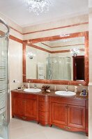 Custom, mahogany washstand below mirror with red marble frame in traditional bathroom with modern ambiance