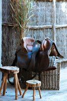 Rustic wooden stool next to saddle on top of basket outdoors