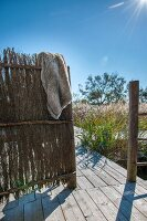 Rustic wooden frame covered with straw mats on wooden terrace