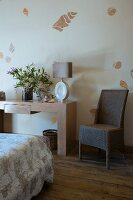 Wicker chair next to vase of flowers and table lamp on modern solid-wood console table against wall with stencilled pattern