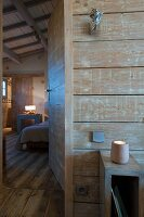 View into bedroom from ensuite bathroom with wooden wall