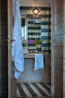 Towel hanging on open door and washstand against tiled wall in rustic bathroom