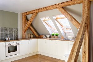 Kitchen in attic room with sloping ceiling and exposed wooden roof structure