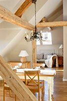 Wrought iron chandelier in attic with exposed wood-beam structure