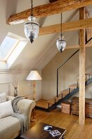 Pendant lamps above sofa in converted attic room with stairs leading to gallery in background