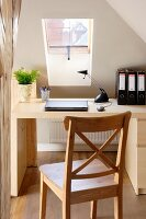 Desk and wooden chair in niche under skylight