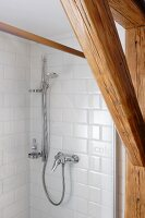 Old wooden beams in front of shower with subway tiles
