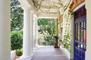 Colonial-style veranda with row of columns in summer garden outside house with blue front door