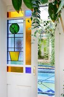 Open sliding door with stained glass panels and view of indoor pool