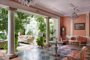 Lounge with chequered tiled floor and row of columns leading into conservatory filled with green plants