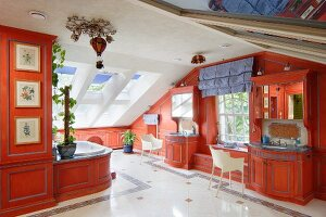 Luxurious bathroom with custom fitted cabinets painted red and armchairs in attic interior