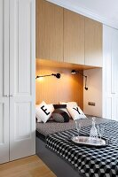 Double bed integrated in niche of fitted wardrobes, black and white bed linen and scatter cushions, glasses and carafe on tray