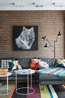 Picture of wolf on brick wall above grey leather sofa with colourful scatter cushions