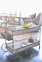 Crockery on delicate serving trolley with lattice trays; wicker chairs and armchair in brightly lit dining area in background