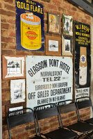 Aufgehängte Vintage-Metallschilder an Ziegelwand, davor ein Reihe schwarze Metallstühle