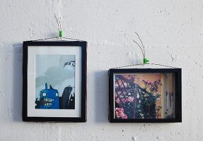 Black-framed pictures hung on wall using wire