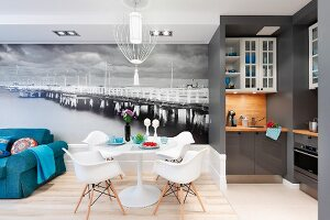 Tulip table, Eames Plastic Armchairs and blue sofa in front of mural wallpaper; open-plan, grey designer kitchen to one side