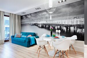 Tulip table, Plastic Armchairs and blue sofa in front of black and white mural wallpaper depicting old pier in the Baltic Sea