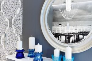 Photo mural depicting old wooden pier reflected in round mirror; blue glass candlesticks in foreground