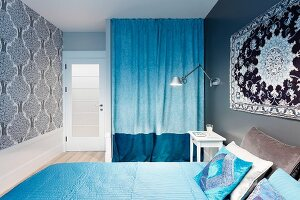 Rug on wall above double bed with pale blue covers, two-tone blue curtain screening wardrobe in niche