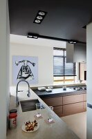 View from open corner into designer kitchen with sink and hob integrated into L-shaped worksurfaces and modern artwork in background