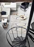 View down black industrial spiral staircase to sofa, large dish on floor used as coffee table and geometric rug