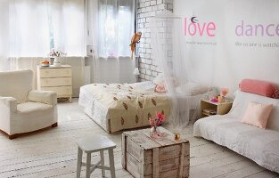 Rustic, shabby-chic bedroom with wooden crate, stool, double bed with canopy and comfortable armchair on pale board floor