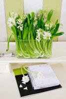 Glass vase of white hyacinths on shelf above desk calendar