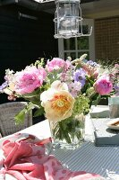 Bouquet of peonies and anemones in glass vase on terrace table