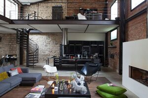 Lounge area and open-plan kitchen in loft apartment with brick and stone walls and view of gallery