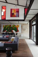 Grey sofas in lounge area and dining area with graffiti-style artwork on wall below encircling gallery in loft apartment