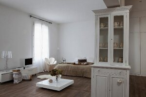 Low white table in bedroom; white vintage dresser in foreground