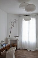 Desk, white chair and floor-length curtains on French windows in bedroom