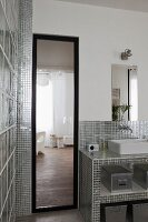 Full-length mirror next to masonry washstand clad in shiny silver mosaic tiled in bathroom