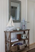 Model boat and lantern on old wooden shelves below framed mirror on white wooden wall